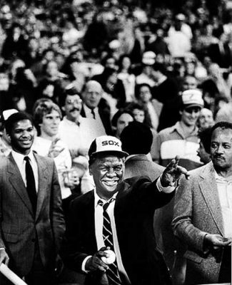 """Chicago's first Black Mayor, Harold Washington prepares to throw out the first ball before the start of a Sox game. One of his staff asst. Bill,""""Doc,"""" Walls is seen just behind his left shoulder and his Corporation Councel Attorney James Montgomery on the right. Photo by Bob Black"""