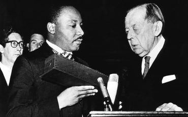 Crown Prince Harald and King Olav of Norway congratulate American civil rights activist Martin Luther King Jr. after he receives the Nobel Peace Prize in Oslo.