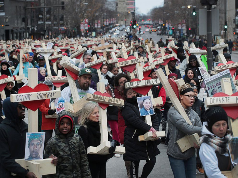 The marchers hold crosses for each kid killed last year.